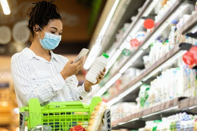 African Woman In Mask Using Smartphone Buying Groceries In Shop