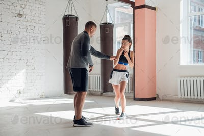 An attractive young boxer teaches his girlfriend boxing techniques in a loft equipped for boxing