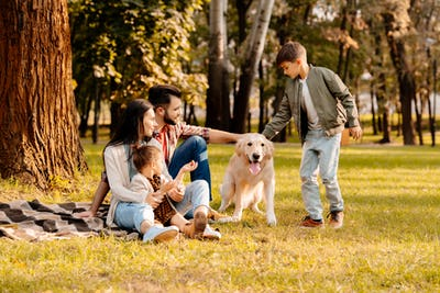 Family sitting on a blanket in a park while son is playing with dog