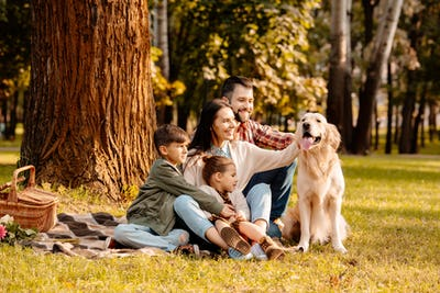 Happy family with two children sitting on a picnic blanket and petting a dog
