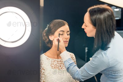 side view of focused makeup artist applying eye shadows on models face in beauty studio