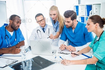 multiethnic team of doctors brainstorming and using laptop