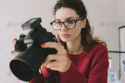beautiful female photographer working with digital photo camera in office