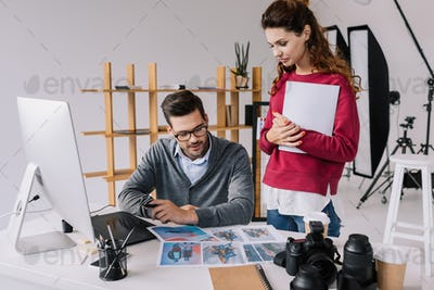 female and male photographers looking on photos in modern office with computer