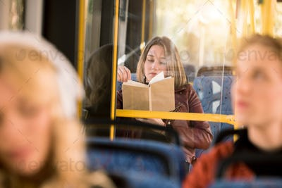 selective focus of young woman reading book in city bus