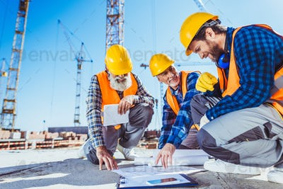 Three construction workers sitting on concrete at construction site, discussing building plans