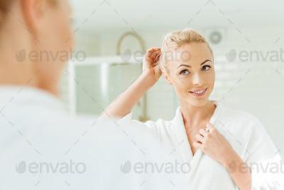 beautiful smiling young woman in bathrobe looking at mirror at morning