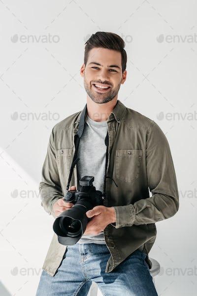 happy professional male photographer with digital photo camera in photo studio