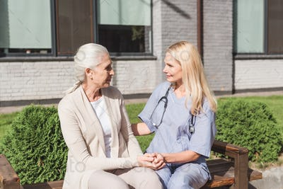 nurse and patient holding hands and smiling each other outside nursing home