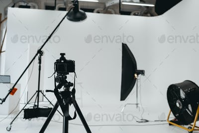 photo studio with digital photo camera, lighting equipment and fan