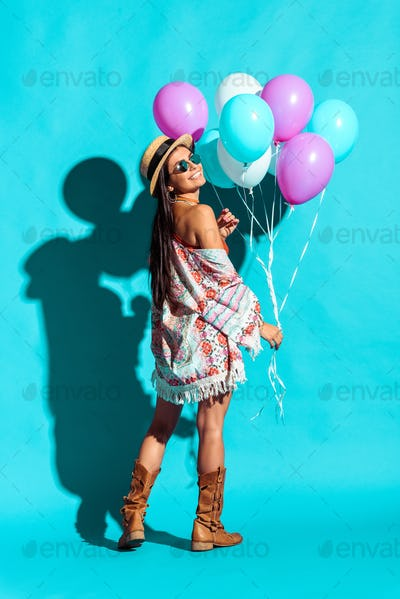 Smiling stylish Hippie girl holding colored balloons