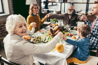 family holding hands and praying on thanksgiving before holiday dinner