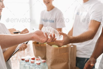 cropped shot of volunteers with food and drinks for charity