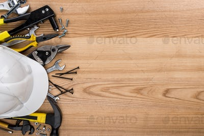 Top view shot of composition with various reparement tools and hardhat on wooden surface