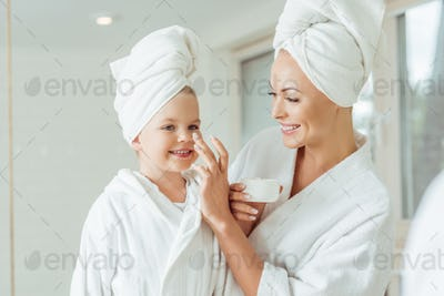 happy mother and daughter in bathrobes and towels applying face cream together