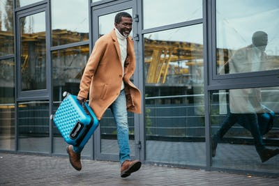 Middle aged African american man hurrying up on plane with a suitcase