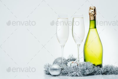 bottle of champagne, wineglasses and christmas decorations isolated on grey