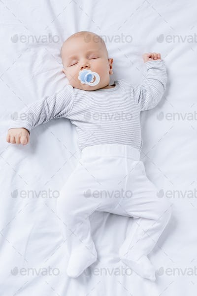 overhead view of baby with pacifier in mouth sleeping on bed