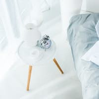 high angle view of alarm clock and coffee cup on table in bedroom