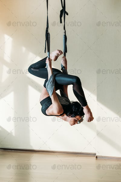 young athletic woman practicing aerial yoga