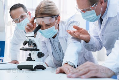 Professional scientists in white coats and sterile masks, doing microscope analysis and discussing