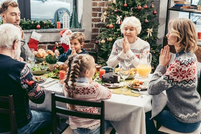 happy european family praying on christmas dinner