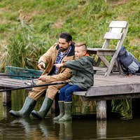 father and son fishing together with rods on wooden pier at lake