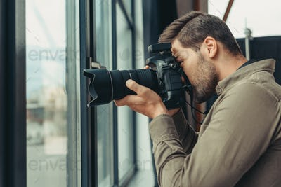 professional male photographer with digital photo camera at window