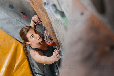 High-angle shot of young woman in sportive attire climbing a wall with grips at gym