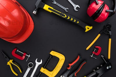 Top view shot of different reparement tools and hard had on black table top