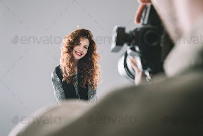 professional photographer taking photos with beautiful model in photo studio with lighting equipment