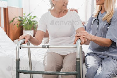 cropped shot of smiling senior woman with walker and nurse holding hands