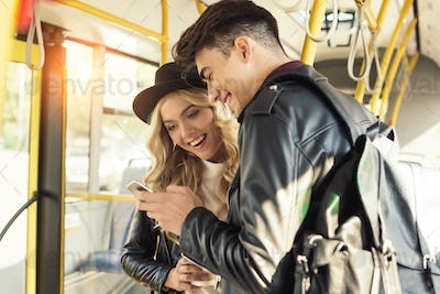 young couple using smartphone while riding in public transport