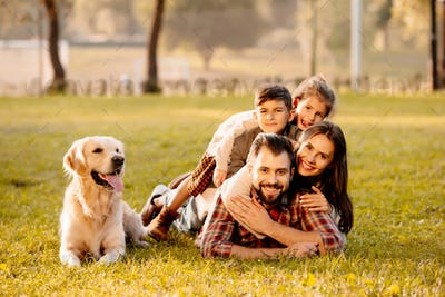 Happy family with two children lying in a pile on grass with dog sitting beside them