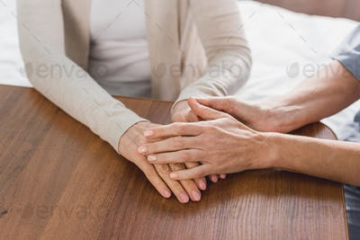 close-up partial view of nurse and senior patient holding hands
