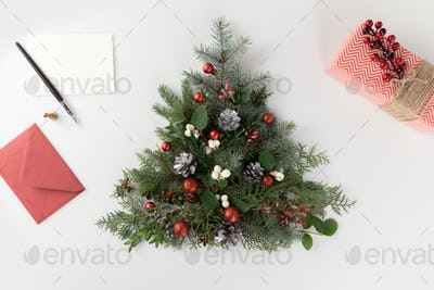 top view of christmas tree made of fir branches, christmas balls and pine cones with letter and