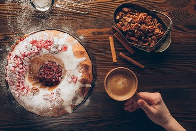 cropped view of female hand with coffee on tabletop with homemade christmas cake, pecan nuts and