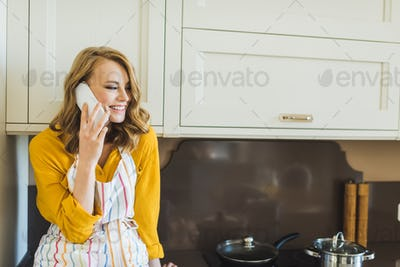 Attractive young woman talking on phone in kitchen