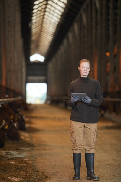 Young Female Worker Holding Tablet at Farm