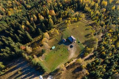 Aerial view of a small countryside homestead and colorful autumn forest. Drone point of view