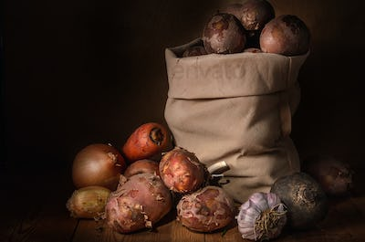 potatoes in a cloth bag and other vegetables
