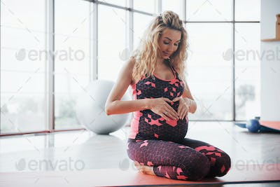 Concept of Yoga and Fitness Pregnancy. Portrait of a young model of a pregnant woman developing