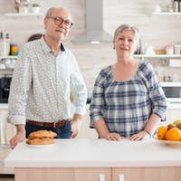 Old cheerful couple looking into camera