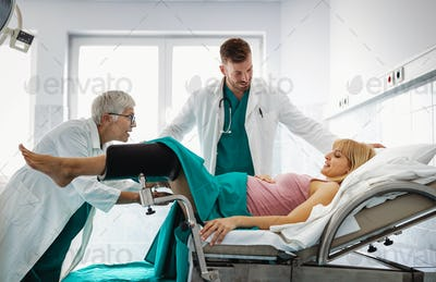Medical team, obstetrician examining pregnant young woman in hospital