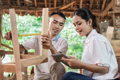 business women use a pad and carpenters measure wood to make crafts