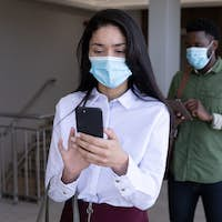 Group of people wearing face masks using smartphones while standing in queue
