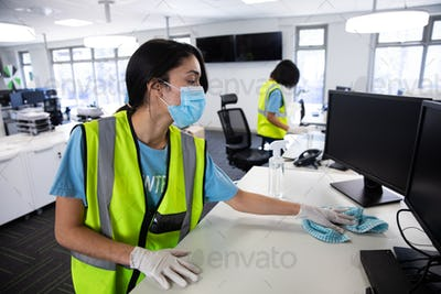 Woman wearing hi vis vest and face mask cleaning the office using disinfectant