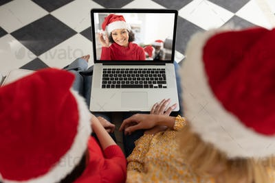 Woman and daughter in Santa hats having a video chat with another woman on her laptop at home