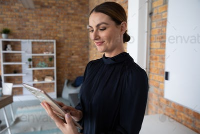 Woman smiling while using digital tablet