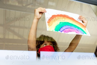 Boy wearing face mask sticking rainbow painting to the window